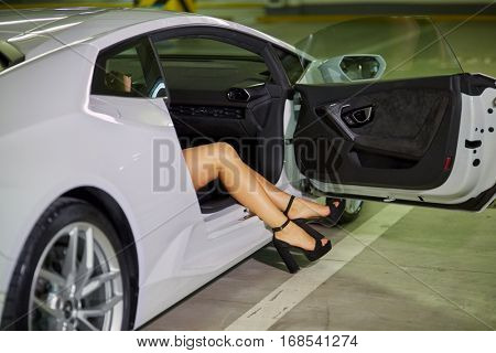 Female legs in high-heel shoes sticking out of modern white car door at underground parking.