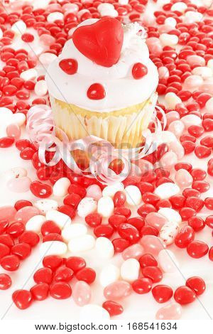 Valentines day cupcake surrounded by heart shaped candy.