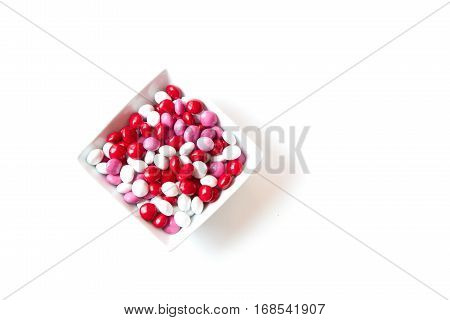 Colorful red white pink coated Valentine candy in a bowl isolated on white background with room for copy space