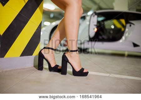 Female legs in high-heel shoes near striped pillar against white car at underground parking.