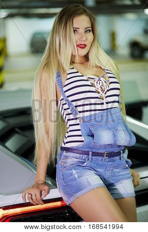 Young smiling woman in striped bodysuit and jeans overall stands leaning back onto trunk of modern white car at underground parking.