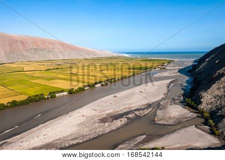 Valley of Ocona River as it flows into the Pacific ocean in the Arequipa Region. Lots of agriculture in the dry landscape in the river valley. Peru