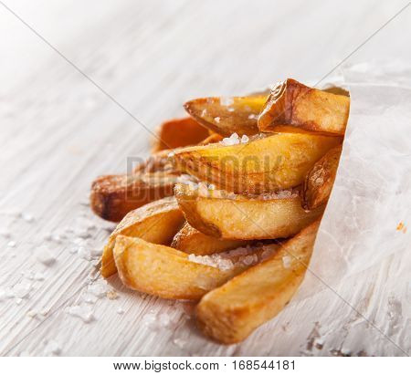 French fries in a little white paper bag on wooden background.