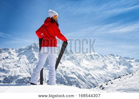 Beautiful brunette woman with ski. Sunny day during winter.