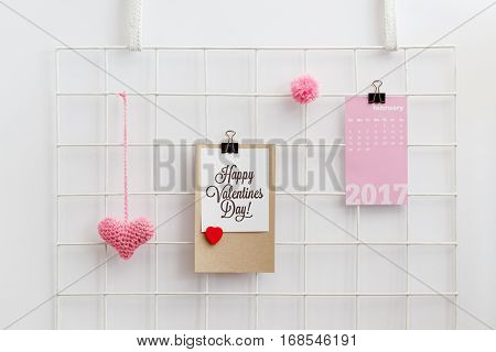 Happy Valentine's Day card on a metal grid display with knitted pink heart and pom pom. Valentine's Day decoration. Wall grid organizer.