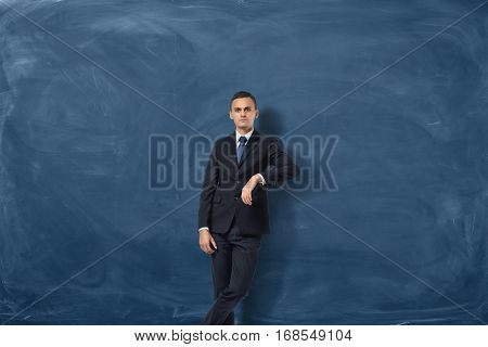 Young businessman is leaning on copy space on the blue chalkboard background. Learship qualities. Confidence. Ready for success