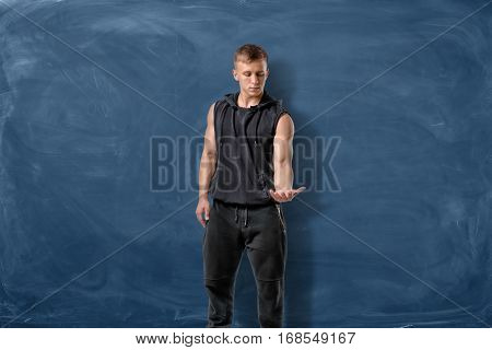 Fit man in black standing on blue chalkboard background and looking at his hand. Fitness and health. Exercising. Sports challenges.