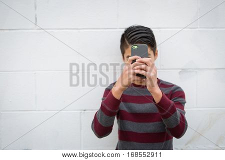 Teenage asian boy standing alone against an outdoor white background holding his smartphone up to obscure his face