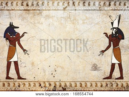 Grunge background with old stucco texture of beige color and Egyptian gods Anubis and Horus images