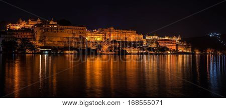 Glowing cityscape at Udaipur by night. The majestic city palace reflecting lights on Lake Pichola travel destination in Rajasthan India