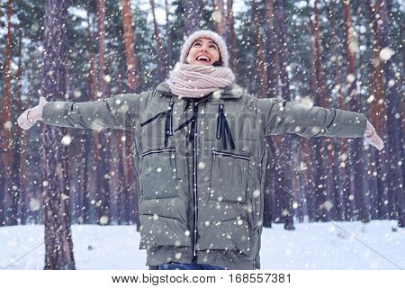 Mid shot of positive lady rejoices snow and winter while standing in the forest. Wearing warm pink knitted cap and scarf. Catching snowflakes in winter