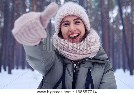 Close-up of happy woman showing ok gesture while standing and walking in the forest on a snowy day. Female wearing warm clothes. One thumb up