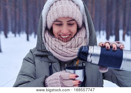 Close-up of female pouring tea from thermos to the cup in a snowy forest. The hand of the woman pouring tea from the thermos in the snowy wood