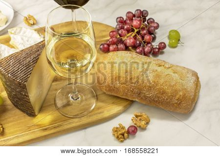 A photo of a glass of white wine with a piece of cheese, white bread, red and white grapes, and walnuts, on a white marble table. Selective focus