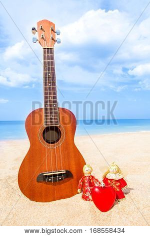two Christmas doll an angel give a Heart on the sand beach and blue sky summer with Ukulele