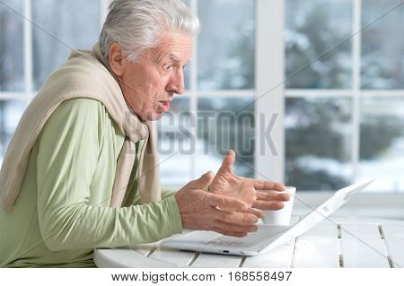 senior man using laptop sitting near window