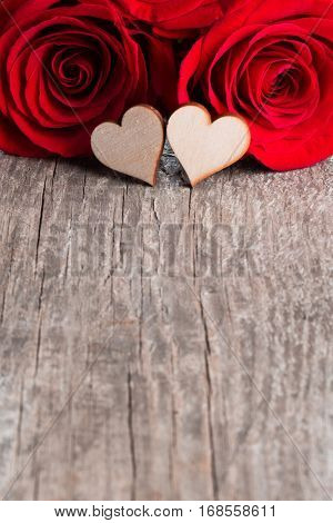 Two roses and wooden hearts on old plank background, Valentines day