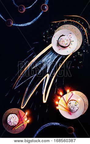 Sweet cupcake on a dark background with a comet tail made from birthday candle