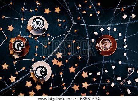 High angle shot of three cups of coffee on a dark background with some scattered star-shaped cookies, chalk drawings of constellations, and