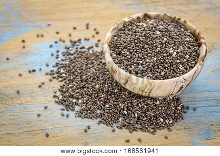 small onyx bowl of chia seeds on grunge wood surface