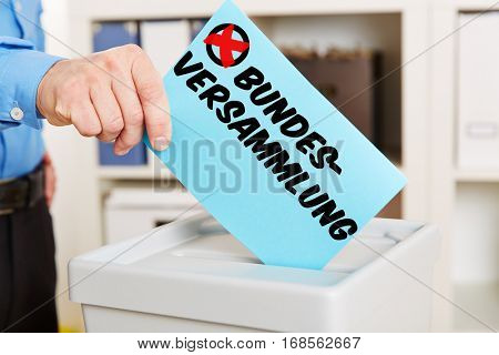 Hand introducing ballot paper with german word