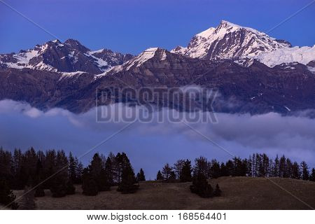 Ecrins National Park mountain peaks (Chaillol Queyrel Tourond) raising above the clouds at dusk. Champsaur Valley. Hautes Alpes Southern French Alps France