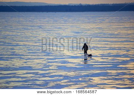 distant fisherman on the frozen river. sunlight