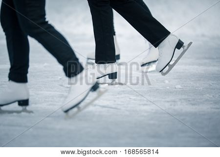 Motion blurred feet of people ice skating outdoors on a pond on a freezing winter day - detail of the legs (color toned image; shallow DOF)