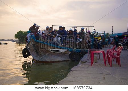 HOI AN, VIETNAM - JANUARY 02, 2016: The overloaded river ferry in evening twilight on the Thu Bon river
