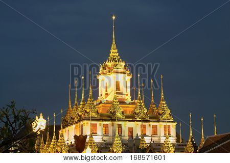 The top of the Chedi Loha Prasat buddhist temple Wat Ratchanadda against the evening sky. Bangkok, Thailand