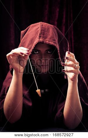 Studio shot of spooky fortune teller with pendulum