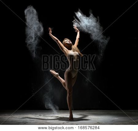 Female sexy long haired blonde in beige bodysuit dancing gracefully on black background white dust cloud all over body studio shot