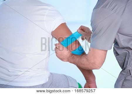 Physiotherapist applying kinesio tape onto patient's arm in clinic, closeup