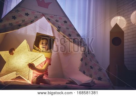 Child in an astronaut costume playing and dreaming of becoming a spacemen. Happy kid plays in tent. Funny lovely girl having fun in children room.