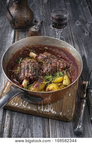 Lamb Knuckles with Potatoes in Burgundy Sauce in Casserole