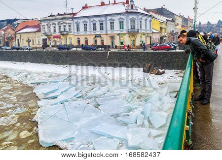 Uzhgorod Ukraine - February 3 2017: A man from the bridge watching the ice drift on the river.