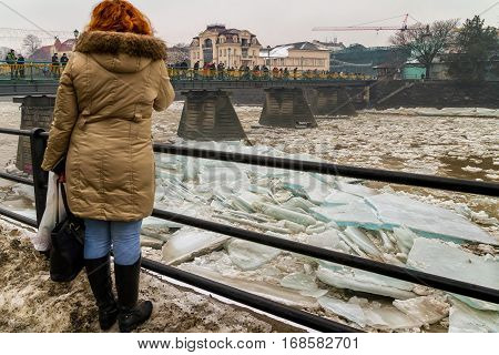 Uzhgorod Ukraine - February 3 2017: A woman from the bridge watching the ice drift on the river.