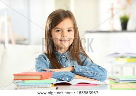 Little girl with books sitting at table