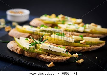 Bruschetta Sandwich With Pear, Blue Cheese, Honey And Nut  On A Dark Background.