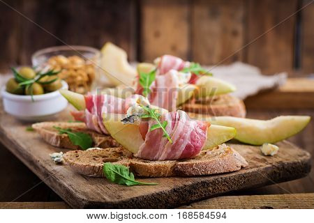 Appetizer With Pear, Prosciutto, Ham, Blue Cheese For Holidays And Toast  On Wooden Background.