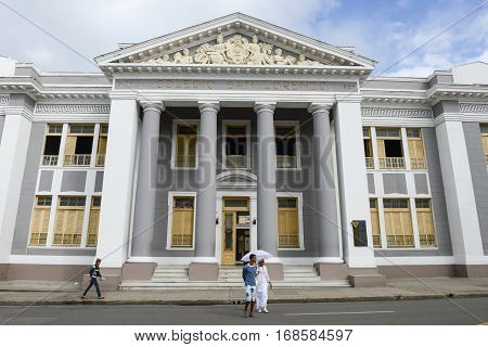 Cienfuegos Cuba - 18 january 2016: People walking in front of San Lorenzo school building. The old town is a UNESCO World Heritage Site.