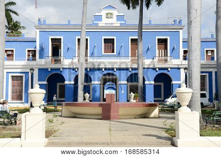 Cienfuegos Cuba - 18 january 2016: people sitting on the benches of the park at customs house in Cienfuegos on Cuba