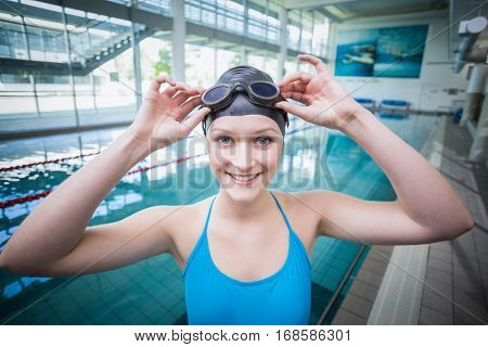 Pretty woman putting on swimming goggles at the pool