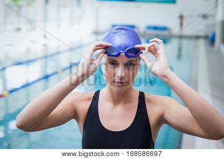 Pretty woman wearing swim cap and goggles at the pool