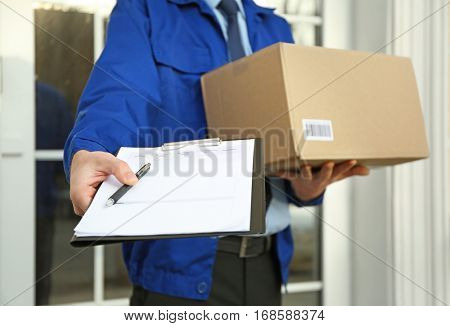 Courier with parcel and clipboard on doorstep, closeup