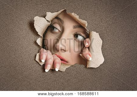 Young Middle eastern woman looking away from ripped paper hole