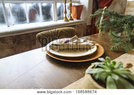 plates of gold on the old oak table in the interior, retro style, vintage, aristocratic manners