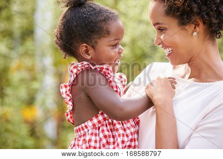 African American mother carries baby daughter and holds hand