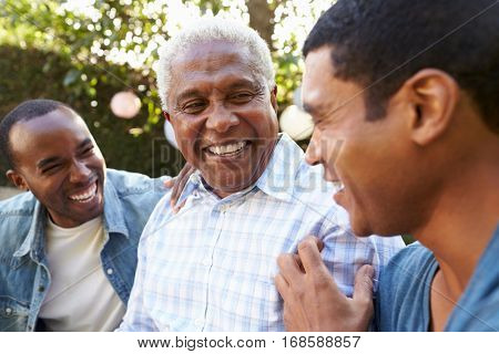 Senior man talking with his adult sons in garden, close up