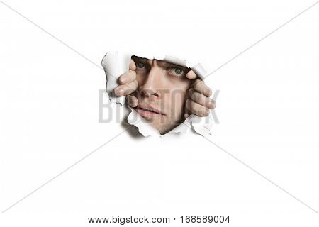 Portrait of a mid adult Caucasian man peeking from ripped white paper hole